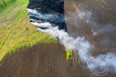 setting fire to the grass in spring. Poisonous dangerous smoke, death of animals, plants, birds and insects, aerial photos, drone. Contrast between the green of the field, arable land and a burnt place