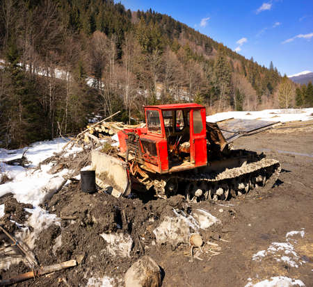 Spring has come in the mountains after winter and heavy tracked tractors are pulling large tree trunks through the mud. Wood is necessary for the country, but harm to ecology and problems to tourism