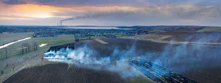 setting fire to the grass in spring. Poisonous dangerous smoke, death of animals, plants, birds and insects, aerial photos, drone. On the horizon - Burshtin thermal power plant, it also smokes 版權商用圖片