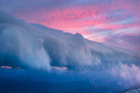 In the Carpathians, on the Borzhava ridge, a morning storm is approaching at sunrise. The storm front of clouds is approaching the mountain