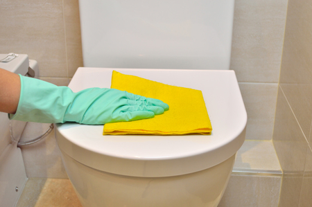 water closet: housemaid cleaning the water closet at the bathroom with yellow cloth and green gloves