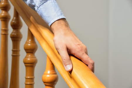 downstairs: man using a railing to go downstairs at home