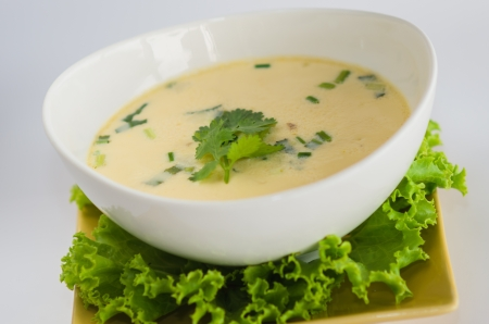 soup with chicken, galanga root and coconut of thailand on white background photo
