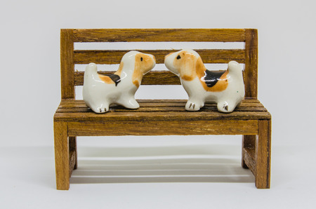 animal figurines: Dog Shih Tzu Cerimic On Wooden Bench In The Park Stock Photo