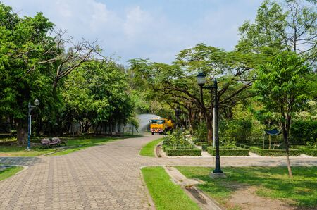 a truck sprays water green trees and plants in sunlight, in a park in Tropical area