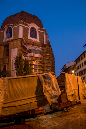 preparing the upcoming market day with old looking mobile booths in front of a church in florence