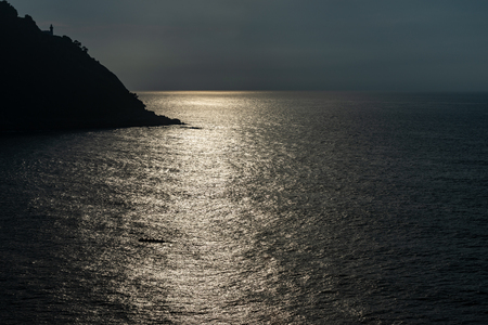 lighthouse of San Sebastian at sunset backlight and reflected sunlight on the sea