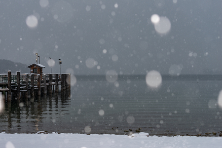 pier on Herrenchiemsee with blowing snow and snowflakes in the foreground
