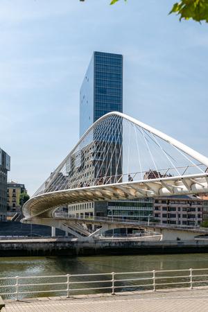 Calatrava pedestrian bridge in Bilbao with an highrise in the background