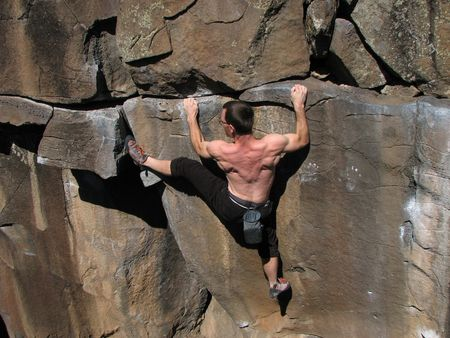 grabbing at the back: Rock climber without a rope strains to climb up