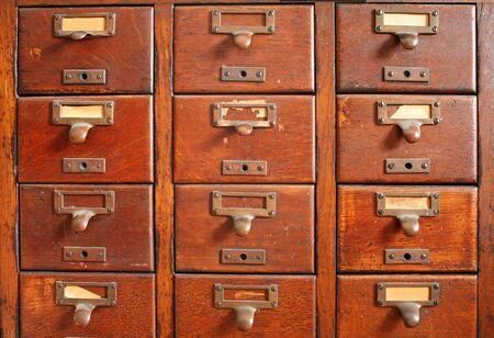 drawers: old wooden card catalog with brass pulls and some old yellowed blank paper labels Stock Photo