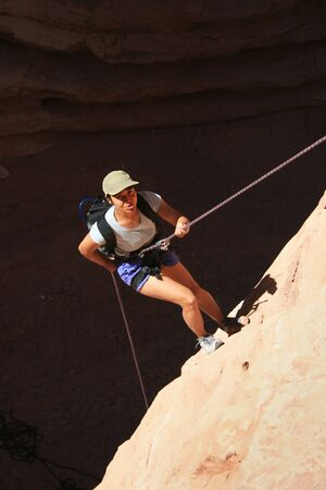 canyoneering asian woman rappels into a shadowed canyon bottom Stock Photo - 3264507