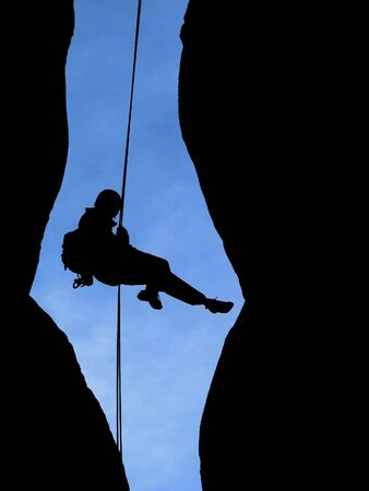 abseil: silhouette of a climber rapelling from the summit of a sandstone tower with a blue sky behind Stock Photo