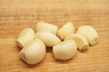 trimmed peeled garlic cloves on a wooden cutting board Stock Photo - 3284665
