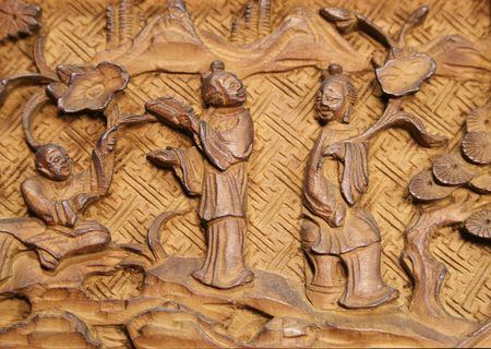 Asian carved wood panel detail with three people