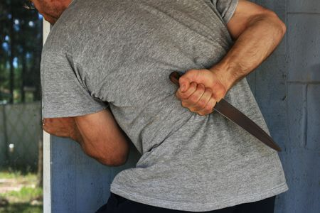 cropped image of a man with a knife behind his back sneaking up to a doorway Stock Photo - 3284855