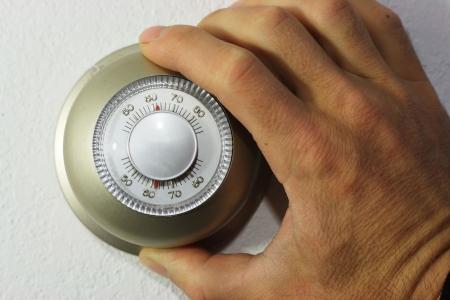 Hand, die einen Thermostat auf 62 Grad Lizenzfreie Bilder