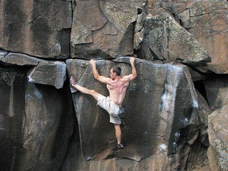 bouldering: un uomo roccia senza una corda si estende per raggiungere un punto d'appoggio