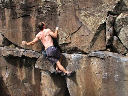 a man rock climbs on a vertical basalt wall without a rope Stock Photo