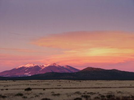 lenticular: the San Francisco Peaks and lenticular clouds in Arizona lit by evening alpenglow Stock Photo