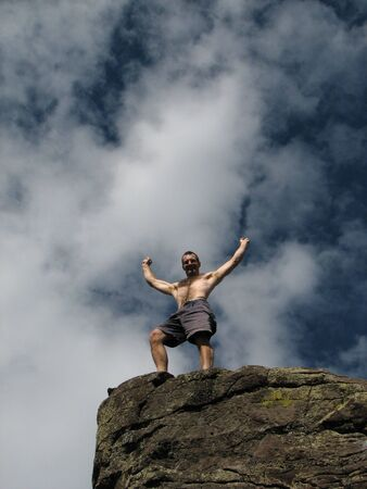 A male climber celebrates reaching the summit with raised arms Stock Photo - 3287088