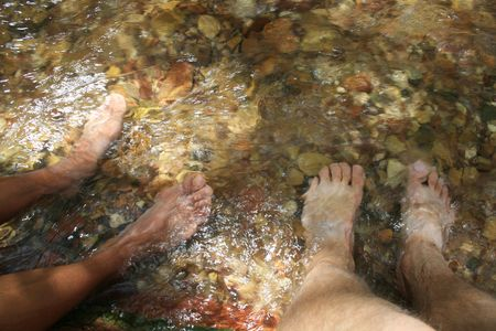a man and woman soaking two pairs of tired feet in a stream from the knee down