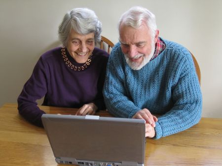 a smiling elder couple looks at a laptop together
