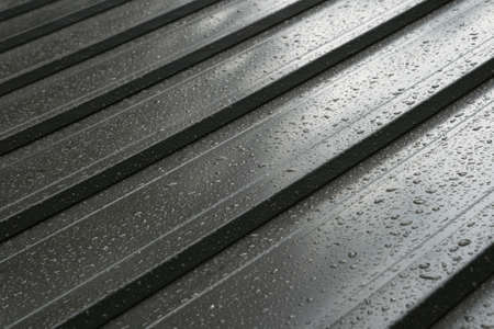dark metal roof detail with raindrops Stock Photo
