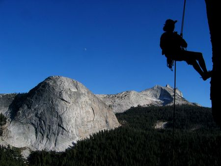 abseil: silhouette of a woman rappelling off of Daff dome, Tuolumne Meadows, Yosemite National Park, California with Fairview dome and Cathedral Peak in the background