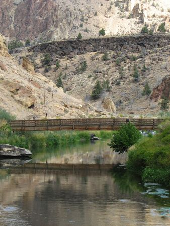 smith rock: vertical image of footbridge over the crooked river, Smith Rock State Park, Oregon