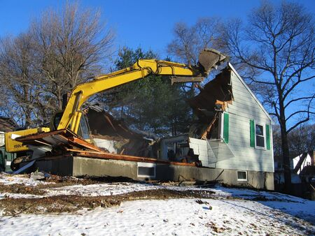un escavatore demolisce una casa in inverno