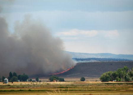 a distant grass fire with flames and clouds of smoke Stock Photo - 3577867