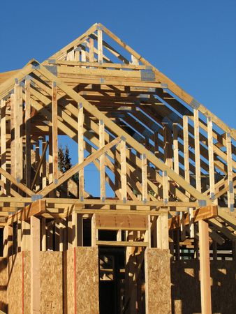 new house under construction showing roof trusses against a blue sky