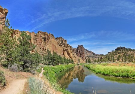 wide-angle image of the reflection of ship rock in the crooked river at Smith Rock State Park Stock Photo