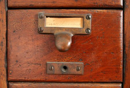 drawers: old wooden card catalog with brass pull and old yellowed blank paper miscellaneous label