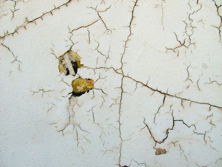 Cracked white painted wall with a hint of old painted wall showing through 版權商用圖片