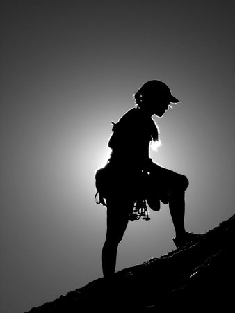 rockclimber: black and white silhouette of a woman climber nearing the summit blocking the sun with diffraction lighting around her