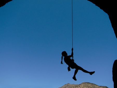 overhanging: silhouette of a woman rock climber hanging by a rope lowering from the top of an overhanging climb Stock Photo