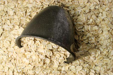 avena en hojuelas: antecedentes de las tierras secas laminadas avena o harina de avena con taza de medida de cuchara Foto de archivo