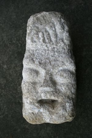 crude stone head carved from gray limestone with a dark gray background Stock Photo - 3587372