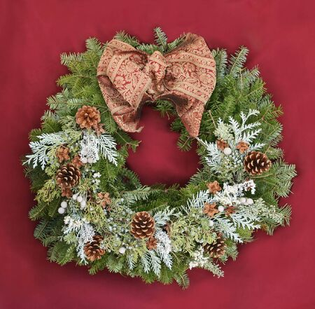 Christmas wreath with a red and gold bow on a red background