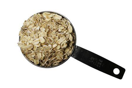 avena en hojuelas: laminadas en seco de harina de avena o avena en un metal media taza Scoop aisladas en blanco  Foto de archivo