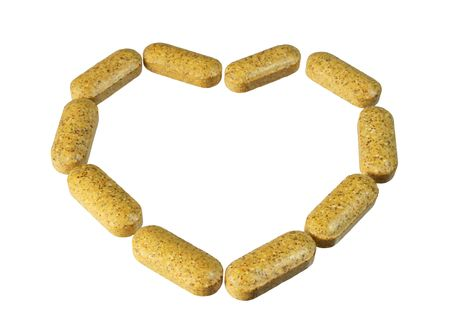 a number of vitamin supplement pills in a heart shape isolated on white