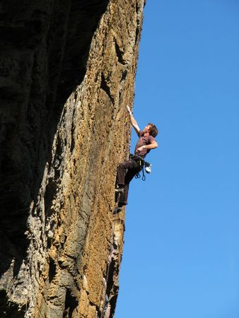 rockclimber: a man climbs up an overhanging rock face on lead