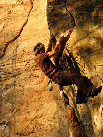 rock climber leading on sandstone in Kentucky in the evening with orange light