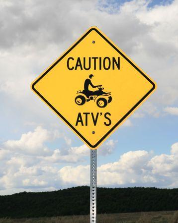 Vorsicht ATV (All-Terrain-Fahrzeug) Schild mit einem bew�lkten Himmel hinter Lizenzfreie Bilder