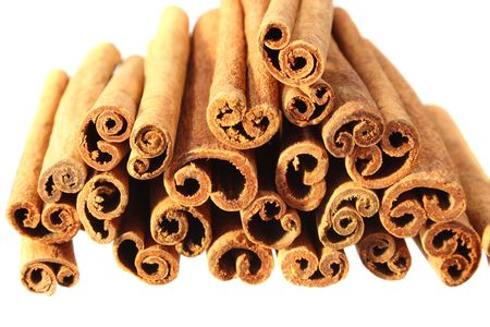 cinnimon: end on view of a pile of cinnamon sticks isolated on white with shallow depth of field Stock Photo