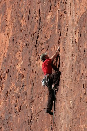 rockclimber: man in red rock lead climbing a red sandstone cliff at Red Rocks, Nevada