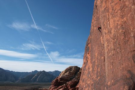 wide angle view of a rock climber in red climbing a tall red sandstone cliff at Red Rocks, Nevada