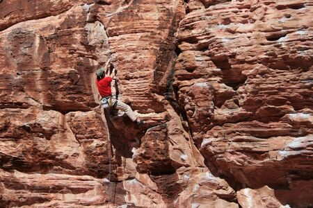 rockclimb: rock climber in red climbing a red sandstone cliff at Red Rocks, Nevada